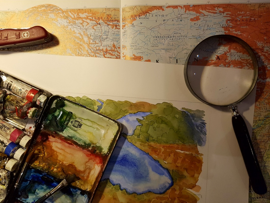 Drawing of watercolors in front of a topographic map