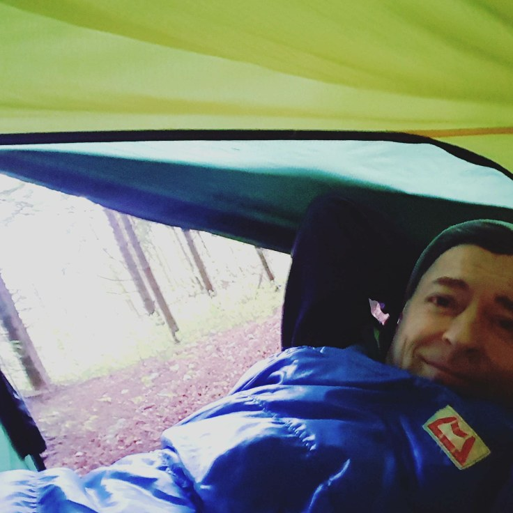 hiker in a tent between trees